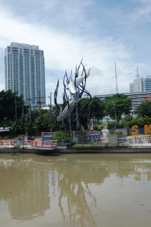 Lambang Kota Surabaya dengan jajaran gedung-gedung bertingkatnya.